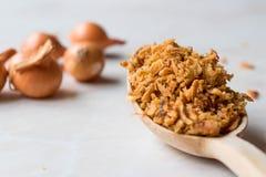 Fried Crispy Onion Flakes med träskeden arkivbilder