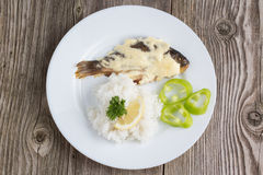 Fried crucian with a garnish. Fried crucian with garnish in a white plate on a wooden background stock photo