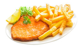 Fried crumbed veal escalope with French fries. Fried crumbed veal escalope with crispy golden French fries served with a lemon wedge and garnished with lettuce stock image