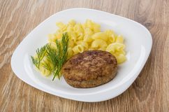 Fried cutlet with pasta and dill in white plate Stock Photography