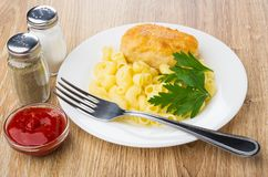Fried cutlet with pasta, ketchup, pepper, salt and fork Stock Images