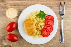 Fried cutlet with pasta in plate, mayonnaise, tomatoes and fork Stock Photography