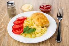 Fried cutlet with pasta in plate, sauces, pepper and fork Stock Photos
