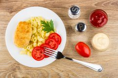 Fried cutlet with pasta in plate, sauces, pepper, salt, tomato Stock Photo