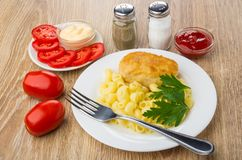 Fried cutlet with pasta, sauces, tomatoes, pepper, salt and fork Stock Photos