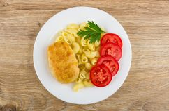 Fried cutlet with pasta, tomatoes in white plate on table Royalty Free Stock Photos