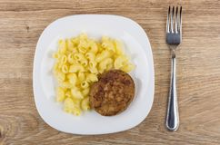 Fried cutlet with pasta in white plate and fork Stock Photos