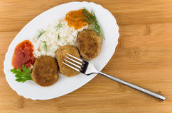 Fried cutlet with rice, squash caviar, ketchup, greens and fork Stock Photo