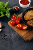 Close up view on burger, cutlets in pan, which stands on cutting board. stock image