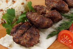 Fried cutlets lie on pita bread with vegetables and greens Royalty Free Stock Image