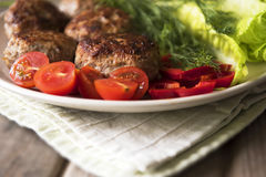 Fried cutlets lie on a plate. With vegetables Royalty Free Stock Photography