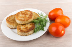 Fried cutlets in plate with dill and tomatoes on table Royalty Free Stock Photo