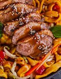 Fried dack meat with egg noodles Stock Photo