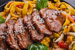 Fried dack meat with egg noodles Stock Photos