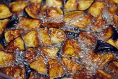 Fried diced eggplant. Eggplant caponata, traditional sicilian dish. Served in a classic ceramic pan over a napkin on an aged wooden table. Surrounded by a silver Stock Photo