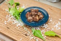 Fried Diced Marinated Beef rare moyen de plat en céramique bleu sur le panneau en bois avec du sel et le légume de mer décorés Photos stock
