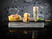 Fried Dim Sum and spring rolls with chopsticks on platter royalty free stock images