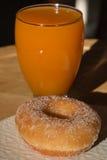 Fried Donut e vetro di succo di albicocca fotografie stock