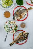 Fried fish dorado on the table. Fried Dorado fish, lettuce and vegetables on the table Stock Photo