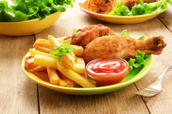 Fried drumsticks with french fries Stock Photo
