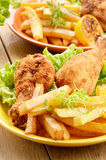 Fried drumsticks with french fries Stock Photography