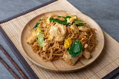 Fried dry instant noodle with chicken and chinese kale in wooden dish on concrete table.  stock image