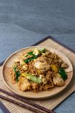 Fried dry instant noodle with chicken and chinese kale in wooden dish on concrete table.  royalty free stock photo
