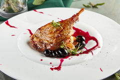 Fried duck leg with mini-pancakes. Cranberry sauce, rosemary and grapes on flat white plate. Gastronomic restaurant menu Stock Photography