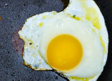 Fried egg. A single fried egg in a black frying pan Stock Photo