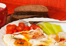 Fried egg. Setting with vegetable and bread Stock Photos