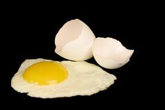Fried egg. With cracked shell on a black background Stock Images