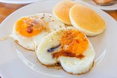 Fried Egg arrosent avec la sauce de soja et le poivre avec le service de crêpe images stock