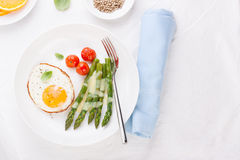 Fried egg with asparagus and tomatoes stock photography