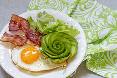 Fried Egg, Bacon and Avocado Rose for Breakfast. Fried Egg, Bacon and Avocado Rose. Low carb high fat breakfast Royalty Free Stock Photo