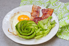 Fried Egg, Bacon and Avocado Rose for Breakfast. Fried Egg, Bacon and Avocado Rose. Low carb high fat breakfast Stock Photos