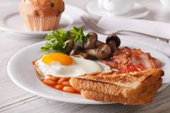 Fried egg with bacon and beans close-up. Horizontal Stock Photos