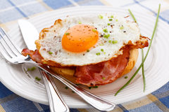 Fried egg with bacon on bread stock images