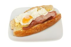 Fried egg and bacon roll. Fried egg and bacon in a crusty roll on a plate isolated against white Royalty Free Stock Photos