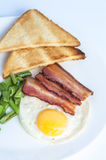 Fried egg, bacon, green beans and toasts on white plate Royalty Free Stock Photo