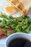 Fried egg, bacon, green beans, toastsand white cup of coffee on light background. English breakfast. Stock Photography