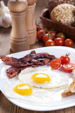 Fried egg and bacon on a plate with spices and vegetables Royalty Free Stock Image
