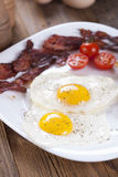 Fried egg and bacon on a plate with spices and vegetables Stock Photo