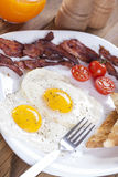 Fried egg and bacon on a plate with spices and vegetables Stock Image