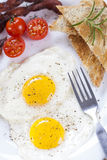 Fried egg and bacon on a plate with spices and vegetables Stock Images