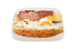 Fried egg and bacon roll. Fried egg and bacon in a giraffe roll on a plate isolated against white stock image