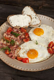 Fried egg with bacon and tomatoes Stock Image