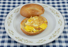 Fried egg bagel sandwich. Fried egg bagel breakfast sandwich on white plate on tablecloth Royalty Free Stock Photo