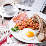 Fried egg with beans, bacon and grilled sausages Royalty Free Stock Photos