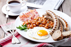 Fried egg with beans, bacon and grilled sausages Royalty Free Stock Photo