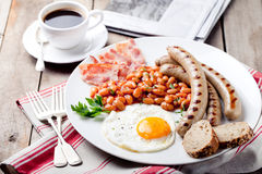 Fried egg with beans, bacon and grilled sausages Stock Images